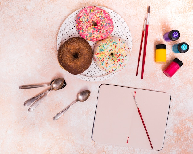 Donuts; paintbrush; spoons and paint bottle on blank notebook over the textured background