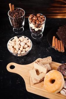 ドーナツ、チョコレートのピーナッツ、木製の背景にコーヒー豆