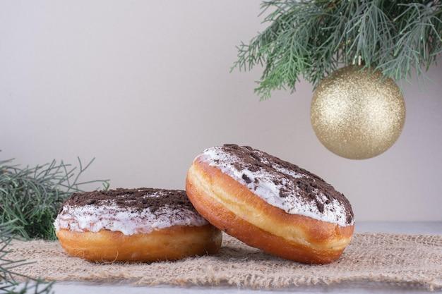 白い表面の装飾的な配置の中に置かれたドーナツ