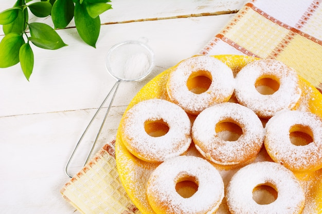 Donuts powdered by caster sugar on checkered napkin