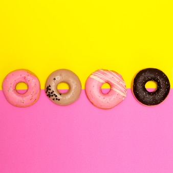 컬러 배경에 도넛 세트입니다. 플랫 레이 패스트 푸드 아트