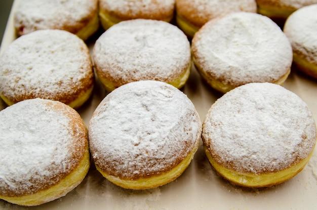 Пончики присыпать сахарной пудрой.