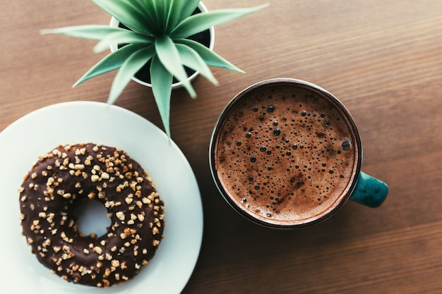 Donuts on the white plate, coffee and green plant on the wooden table