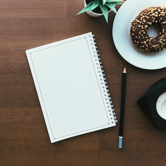 Donuts on the white plate, notebook and coffee on the wooden table. high quality photo