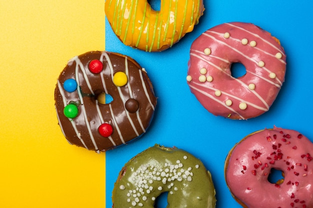 色付きの背景にさまざまな詰め物のドーナツ