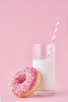 ピンクのミルクのグラスとドーナツ