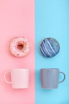 Пончики с глазурью и чашки кофе на пастельных синего и розового пространства. сладкие пончики.