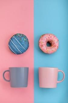 Пончики с глазурью и чашки кофе на пастельно-синей и розовой поверхности