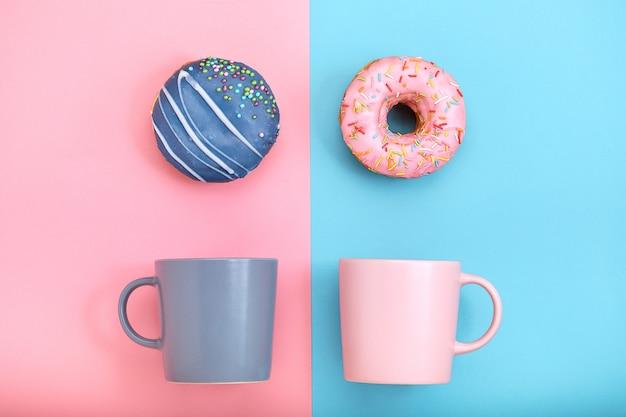 Пончики с глазурью и кофейными чашками на пастельно-голубой и розовой поверхности, сладкие пончики.