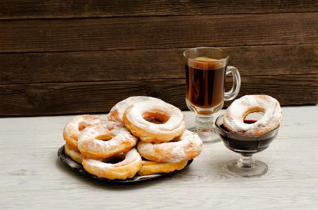 Пончики с сахарной пудрой, кружкой чая и вареньем из смородины на деревянном фоне