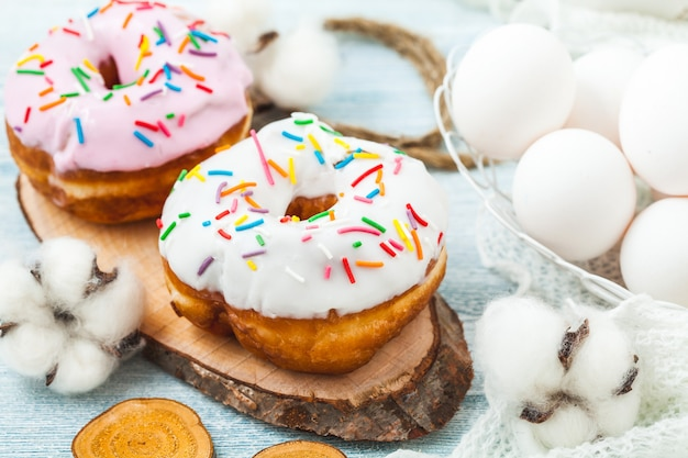 Donuts with icing on a white table, white eggs, easter concept