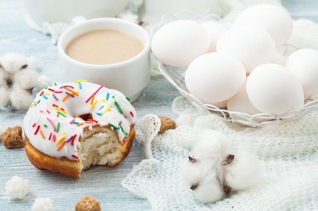 Donuts with icing on a white table, white eggs