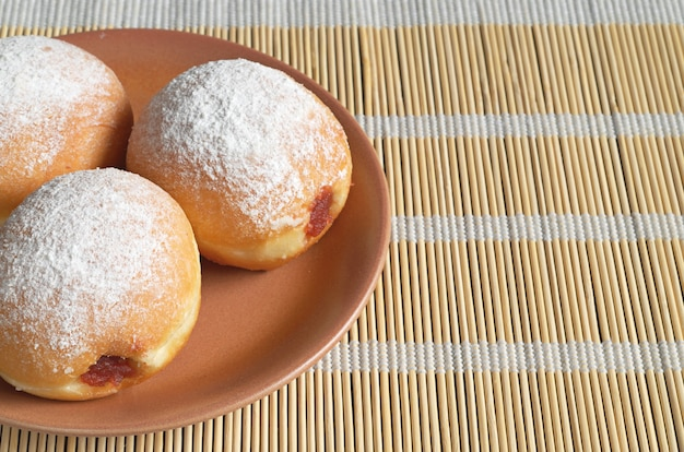 Donuts with jam in brown plate on bamboo napkin