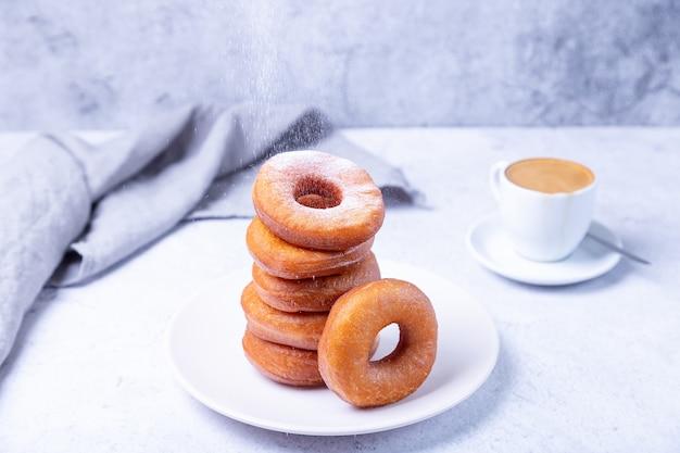 Пончики с сахарной пудрой и чашкой кофе. традиционные пончики в форме кольца, обжаренные в масле. нездоровая, но вкусная еда. крупный план, светлый фон.