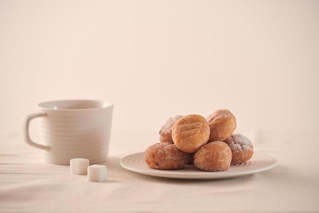 皿に砂糖と白い背景の上のコーヒーカップとドーナツ
