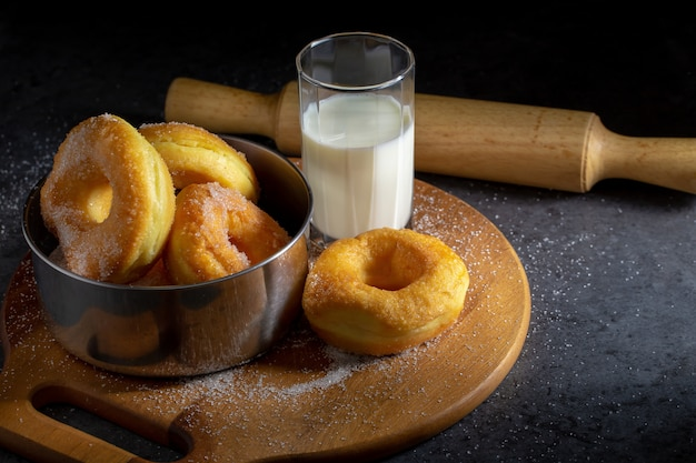 Donuts with sugar on a wooden plate over a dark table background.