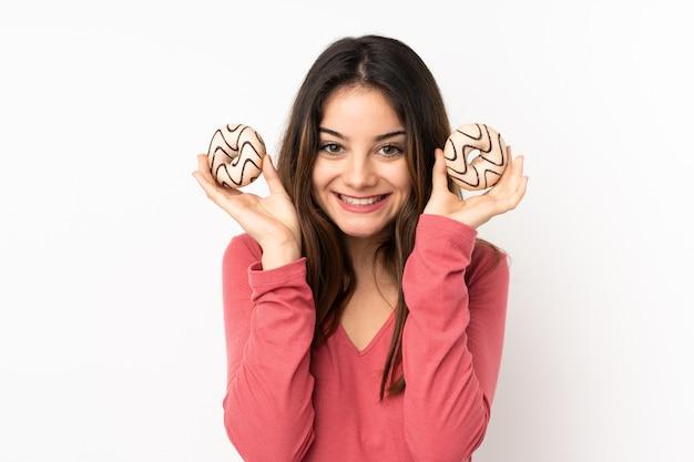 Молодая кавказская женщина изолированная на розовой стене держа donuts