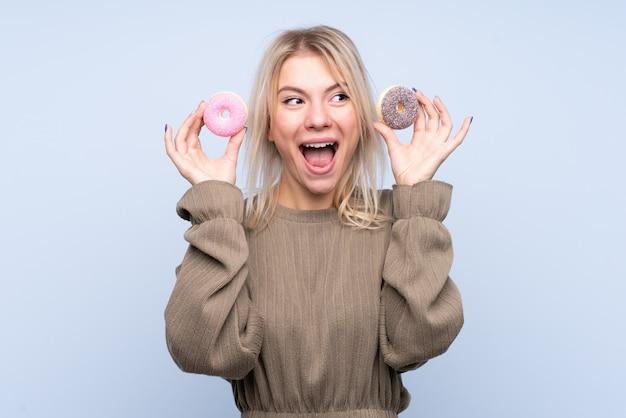 Молодая белокурая женщина над изолированной голубой стеной держа donuts и удивлена