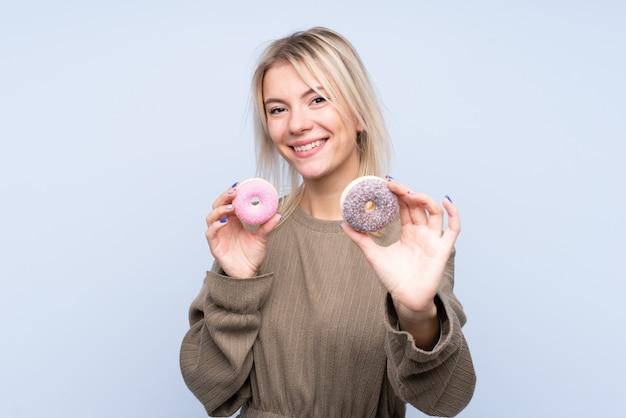 Молодая белокурая женщина над изолированной голубой стеной держа donuts с счастливым выражением