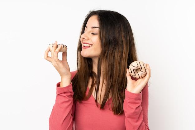 Молодая кавказская женщина на розовой стене держа donuts с счастливым выражением