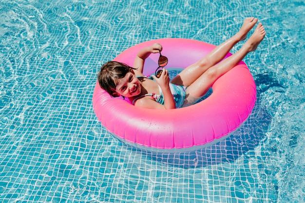 Красивая девушка ребенк плавая на розовые donuts в бассейне. носить солнцезащитные очки и улыбаться. веселый и летний образ жизни