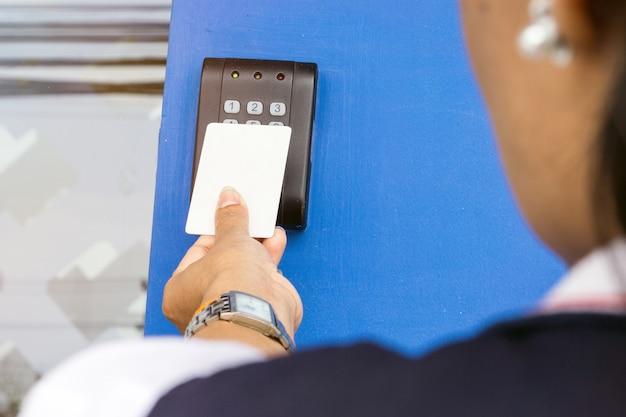 Контроль доступа двери - молодая женщина, держащая ключевую карту, чтобы заблокировать и разблокировать дверь.