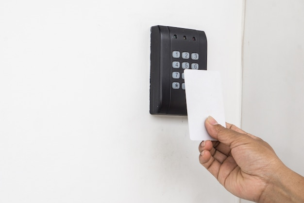 Door access control - young woman holding a key card to lock and unlock door., keycard