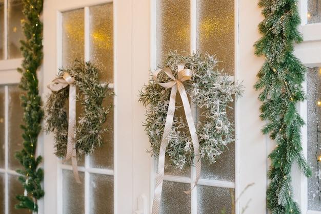 Дверь украшена на рождество вечнозелеными венками