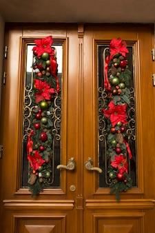 モミの枝、花、ボールで飾られたドア。クリスマスの装飾