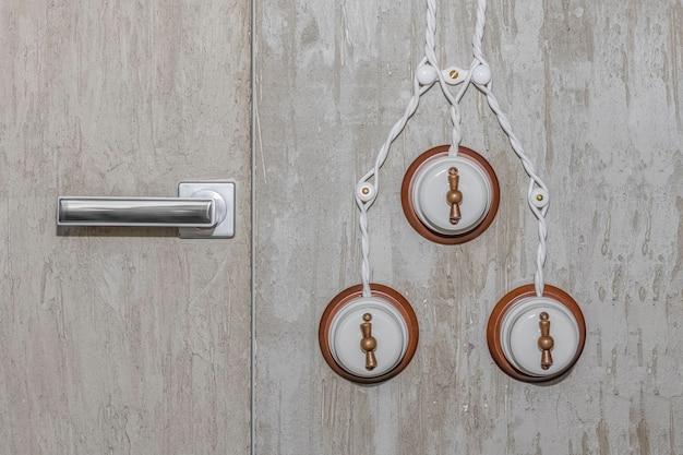 문 손잡이와 장식용 석고가 있는 벽에 있는 3개의 흰색 복고풍 조명 스위치