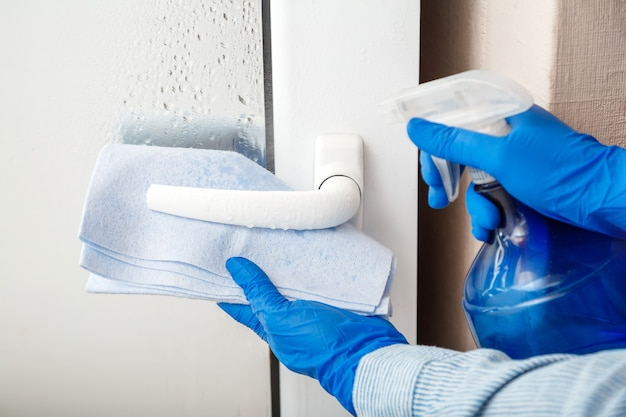 Door handle cleaning by antibacterial alcohol spray woman houseworker in rubber blue gloves clean door knob by cloth rag new normal covid  coronavirus in surfaces disinfection