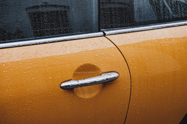 A door handle of a wet yellow car