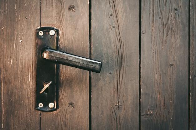 Door handle with a key on a wooden door