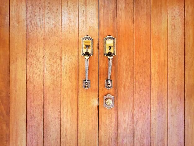 Дверные ручки и отверстие для ключа на закрытой коричневой деревянной двери