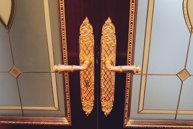 오래된 이중 문이있는 문 손잡이. 고전적인 스타일. 더블 골동품 골드 도금 닫습니다.