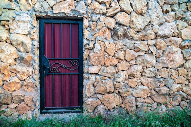 The door is in a rock wall. background of limestone masonry.