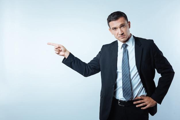 ドアがあります。真面目で素敵なハンサムなビジネスマンが左を指して、あなたを解雇しながらあなたを見ています