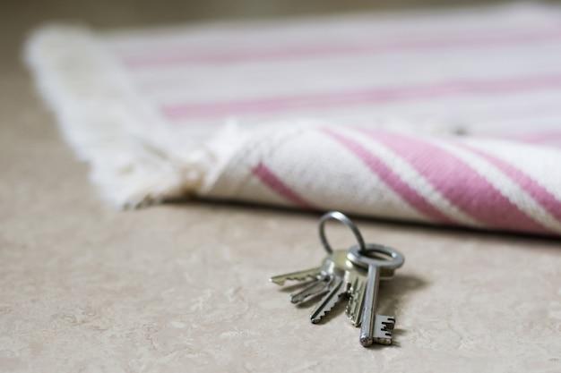 흰색과 분홍색 스트립이있는 도어 매트와 아래에 숨겨진 키를 드러내는 들어 올린 가장자리