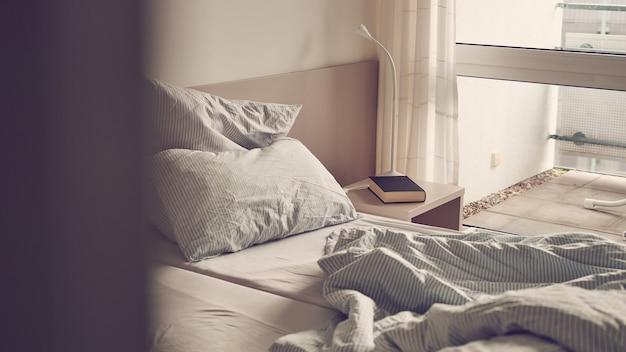 Дверь комнаты приоткрытая, с неубранной кроватью