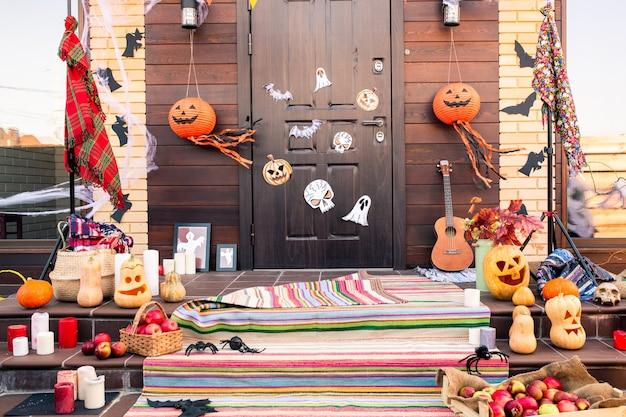 Дверь загородного дома, украшенная символами хэллоуина, перед лестницей с джек-фонарями, пауками, летучими мышами, яблоками и свечами
