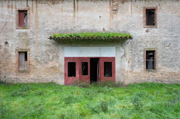 Door of a ruined building with vegetation