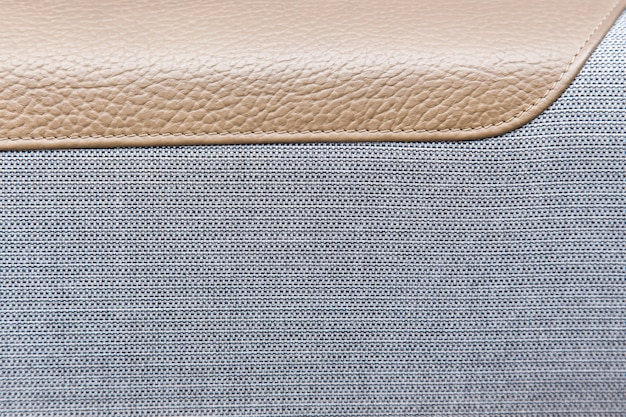 Door trim of gray textiles and leather in a luxury car.