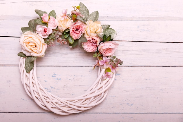 Door wreath made of artificial flowers and autumn plants on shabi white wooden background.