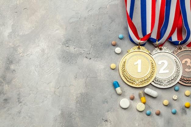 アスリートのためのドーピング。金、銀、銅メダルと灰色の背景にカプセルと丸薬。