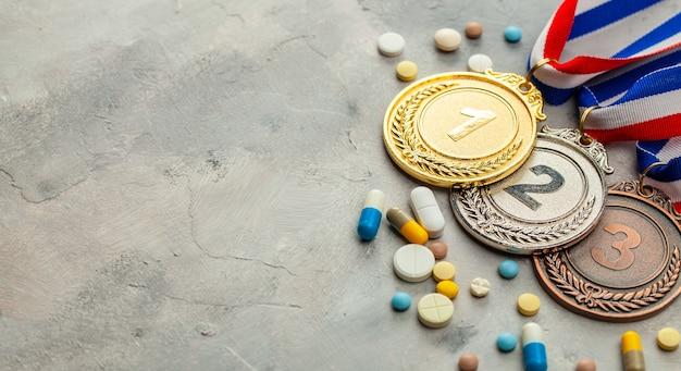 Допинг для спортсменов. золотая, серебряная и бронзовая медаль и таблетки с капсулами на сером фоне.