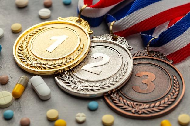 アスリートのためのドーピング。金、銀、銅のメダルと、灰色の表面にカプセルが付いた錠剤。