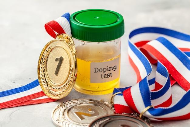 ドーピングテスト。金、銀、銅メダルと灰色の表面の尿分析用の瓶。
