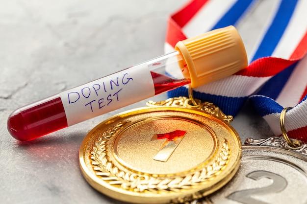 ドーピングテスト。金、銀、銅メダルと、灰色の表面に血液が入った試験管。