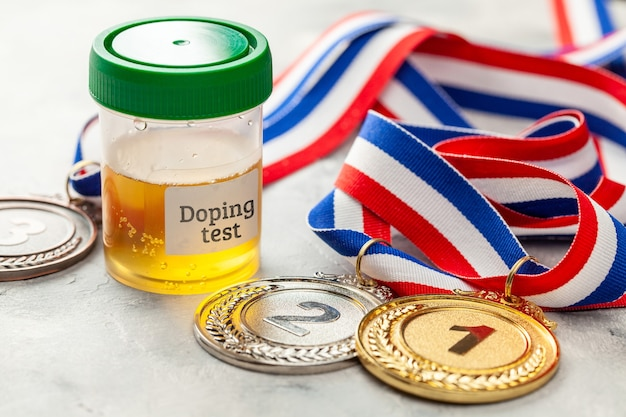 Doping test. gold, silver and bronze medal and a jar for urine analysis on a gray background.