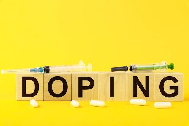 ドーピング、テキストは黄色の背景と医療用注射器の木製の立方体に書かれています。